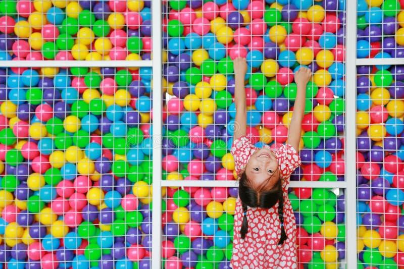 Pequeña muchacha asiática feliz del niño que juega subida y que cuelga en la jaula de la bola colorida del juguete del patio con  fotografía de archivo