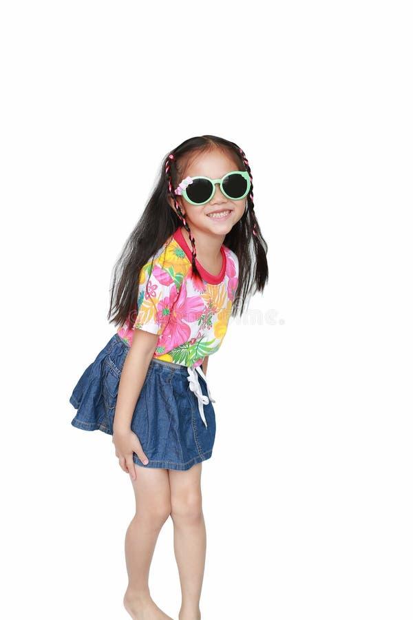 Pequeña muchacha asiática feliz del niño que lleva un vestido y las gafas de sol del verano de las flores aislados en el fondo bl imagenes de archivo