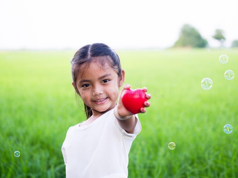 Pequeña muchacha asiática feliz que celebra el corazón y la sonrisa rojos imagenes de archivo