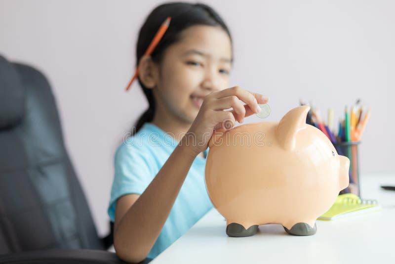 Pequeña muchacha asiática feliz que pone la moneda del dinero en la profundidad baja del foco selecto de la hucha del campo imágenes de archivo libres de regalías