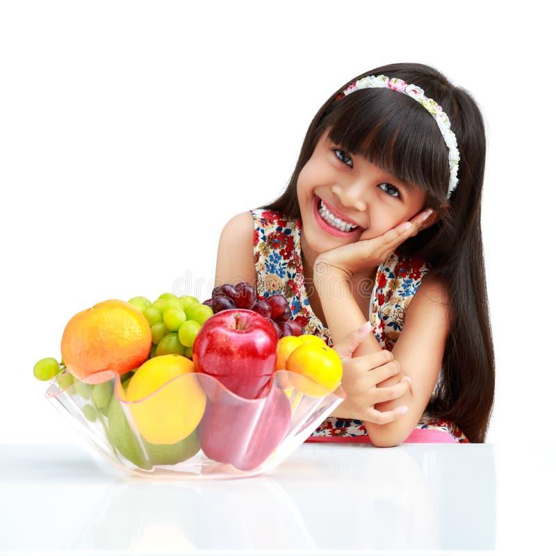 Pequeña muchacha asiática feliz que se sienta en la tabla con la placa de la fruta imagenes de archivo