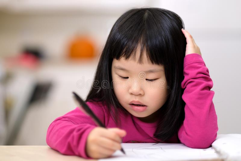 Pequeña muchacha asiática joven que aprende escribir imagen de archivo
