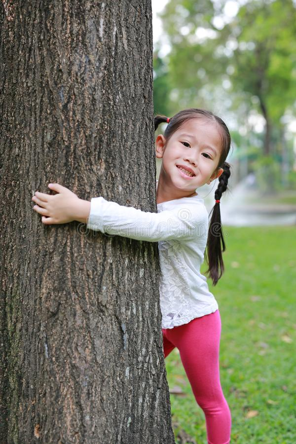 Pequeña muchacha asiática linda del niño que abraza un árbol grande en el jardín fotografía de archivo libre de regalías