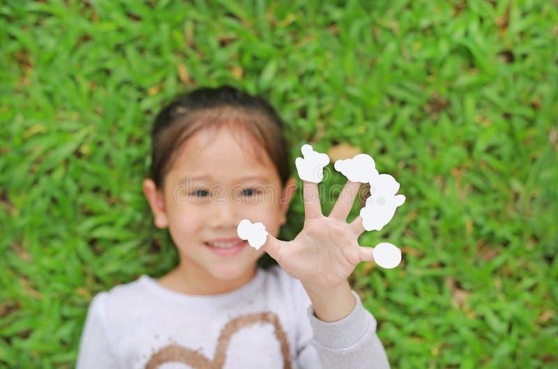 Pequeña muchacha asiática linda del niño que miente en césped de la hierba verde con las etiquetas engomadas blancas vacías de la imágenes de archivo libres de regalías