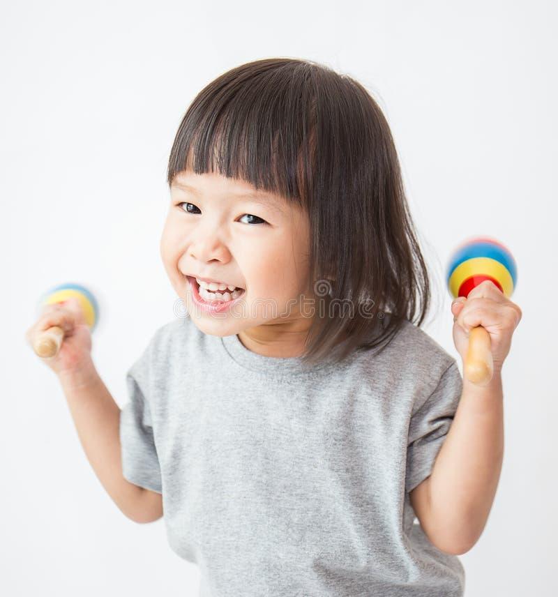 Pequeña muchacha asiática linda que juega los maracas fotografía de archivo libre de regalías