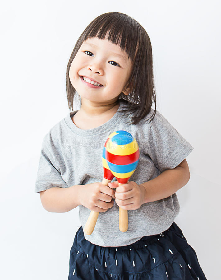 Pequeña muchacha asiática linda que juega los maracas fotos de archivo libres de regalías