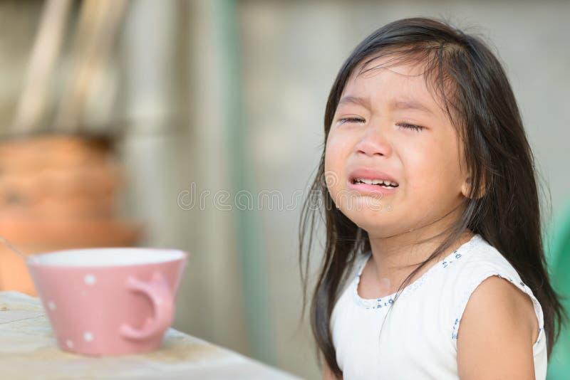 Pequeña muchacha asiática linda que llora porque no coma el desayuno foto de archivo