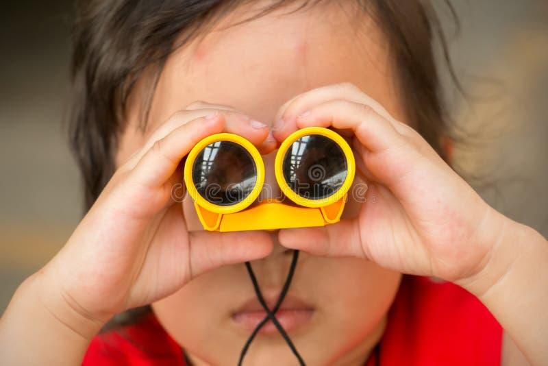 Pequeña muchacha asiática mirando el canal prismáticos fotos de archivo