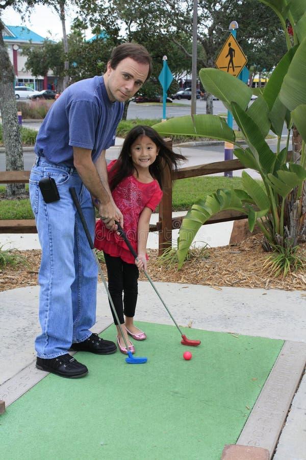 Pequeña muchacha asiática que juega a mini golf con el papá fotos de archivo