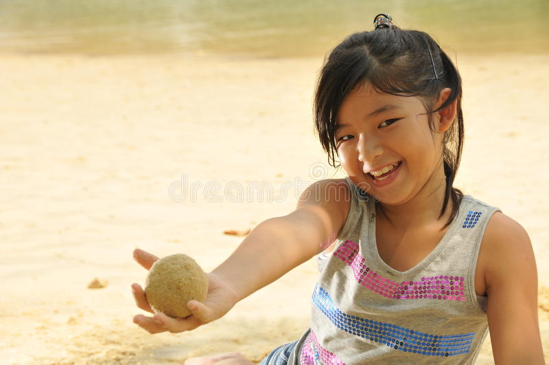 Pequeña muchacha asiática que se divierte por la playa fotos de archivo