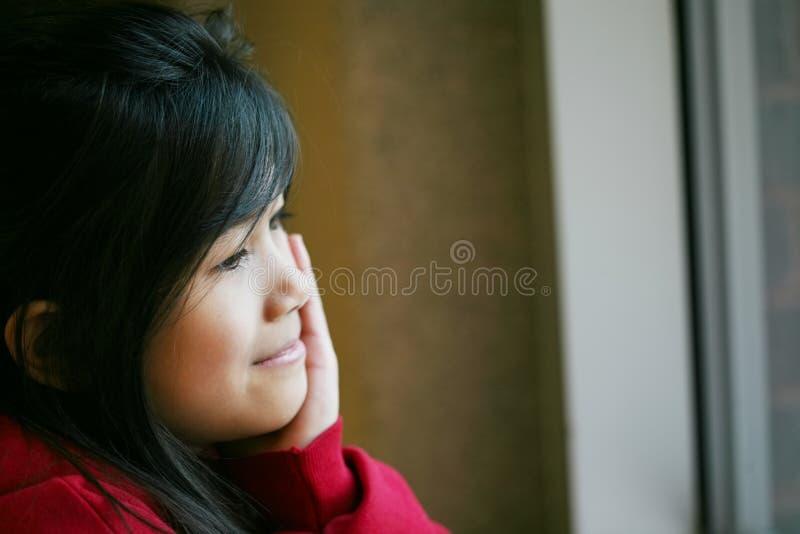 Pequeña muchacha asiática que se sienta reservado por la ventana fotos de archivo