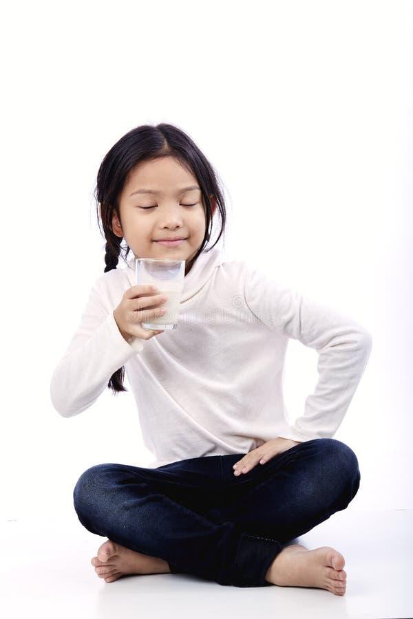 Pequeña muchacha asiática que sostiene un vidrio de leche fotografía de archivo
