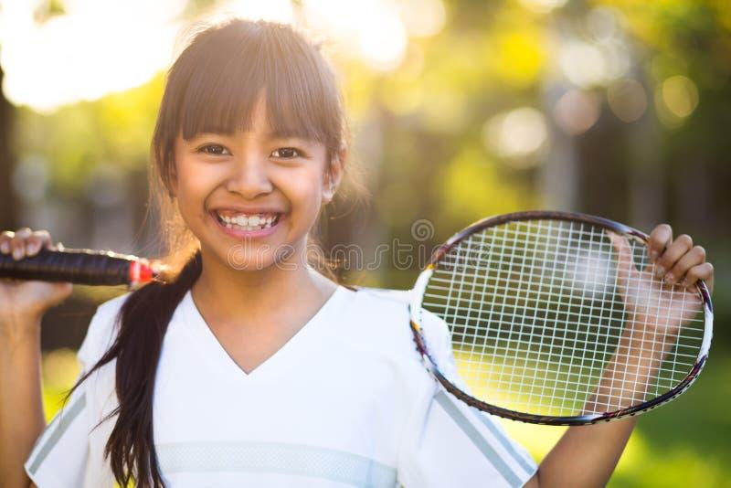Pequeña muchacha asiática que sostiene una estafa de bádminton fotografía de archivo
