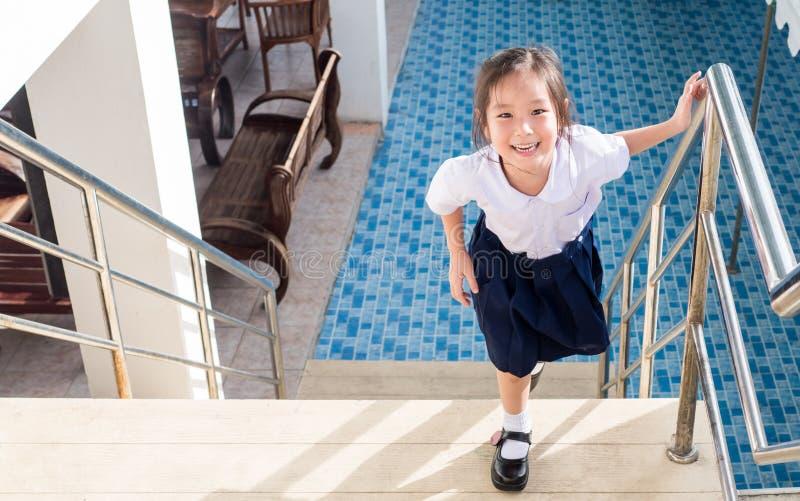 Pequeña muchacha asiática que va para arriba las escaleras en la escuela imagenes de archivo