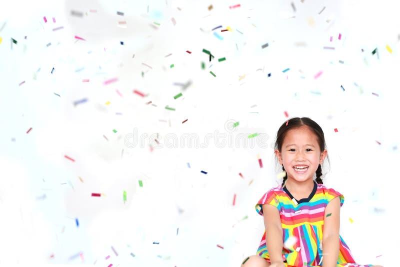 Pequeña muchacha asiática sonriente del niño con muchos pedazos minúsculos coloridos del confeti que caen en el fondo blanco Feli imagen de archivo libre de regalías