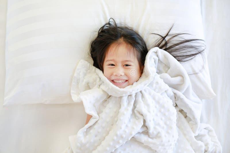 Pequeña muchacha asiática sonriente del niño que miente en cama con la manta y la mirada de la cámara Sobre la visión fotos de archivo libres de regalías