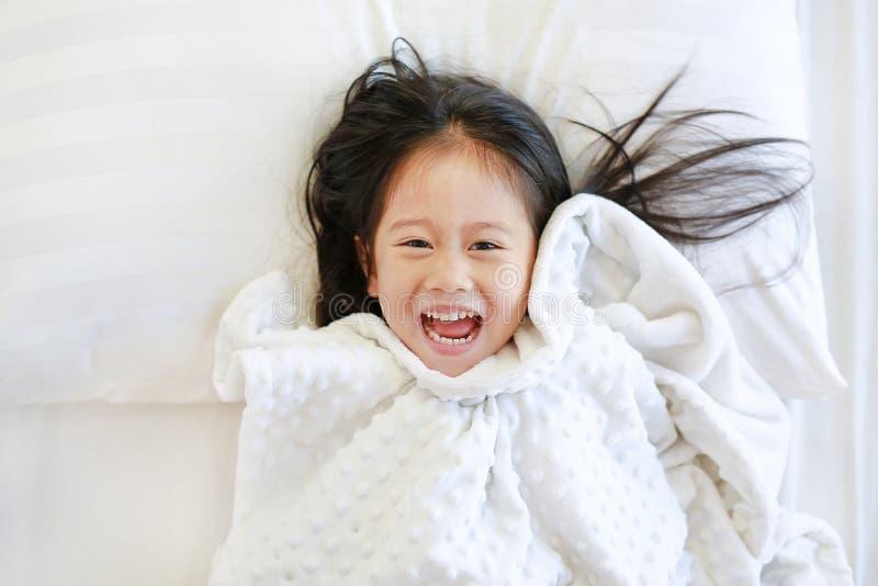 Pequeña muchacha asiática sonriente del niño que miente en cama con la manta y la mirada de la cámara Sobre la visión fotos de archivo
