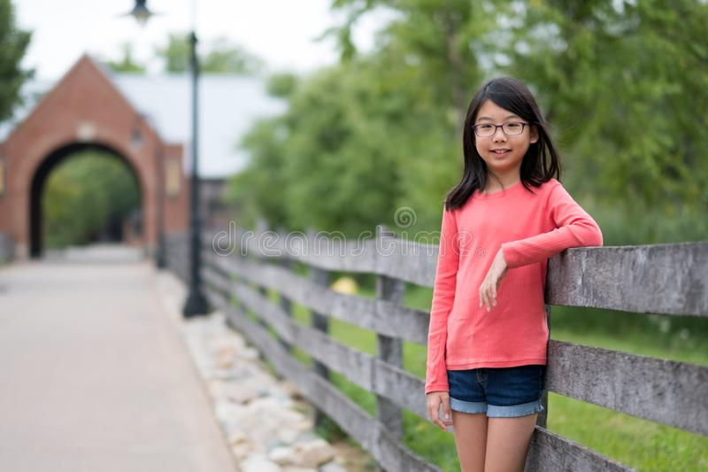 Pequeña muchacha asiática sonriente que se coloca en el parque imagen de archivo libre de regalías