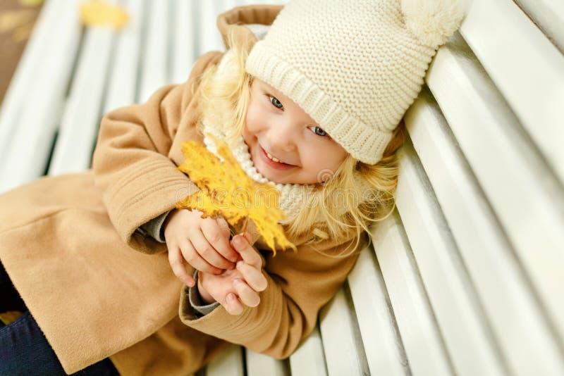Pequeña muchacha bonita en una capa beige que se sienta en un banco y un laughi foto de archivo libre de regalías