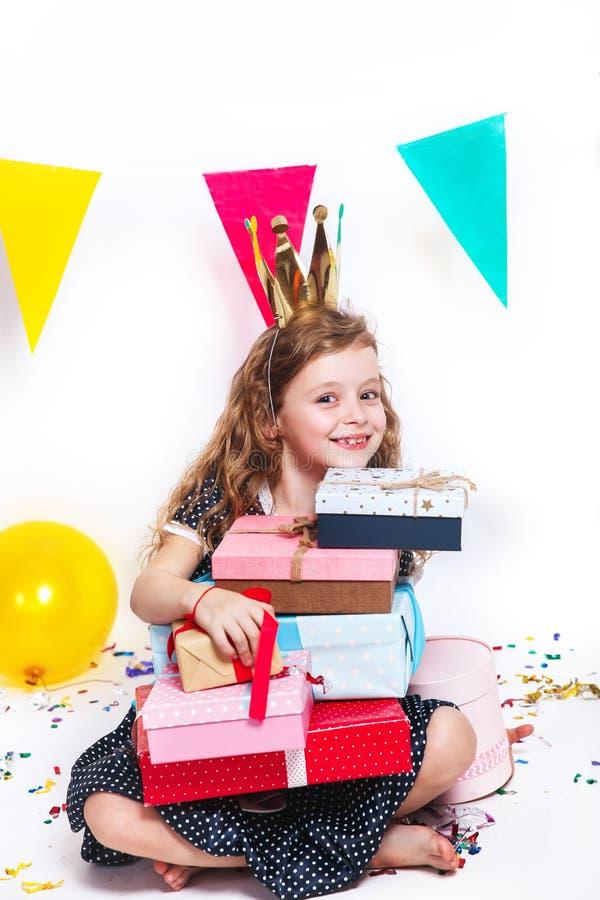 Pequeña muchacha bonita feliz que se sienta con los presentes en la fiesta de cumpleaños imágenes de archivo libres de regalías