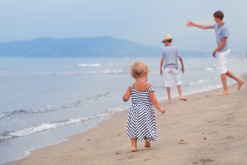 Pequeña muchacha bonita que camina en orilla de mar imagenes de archivo