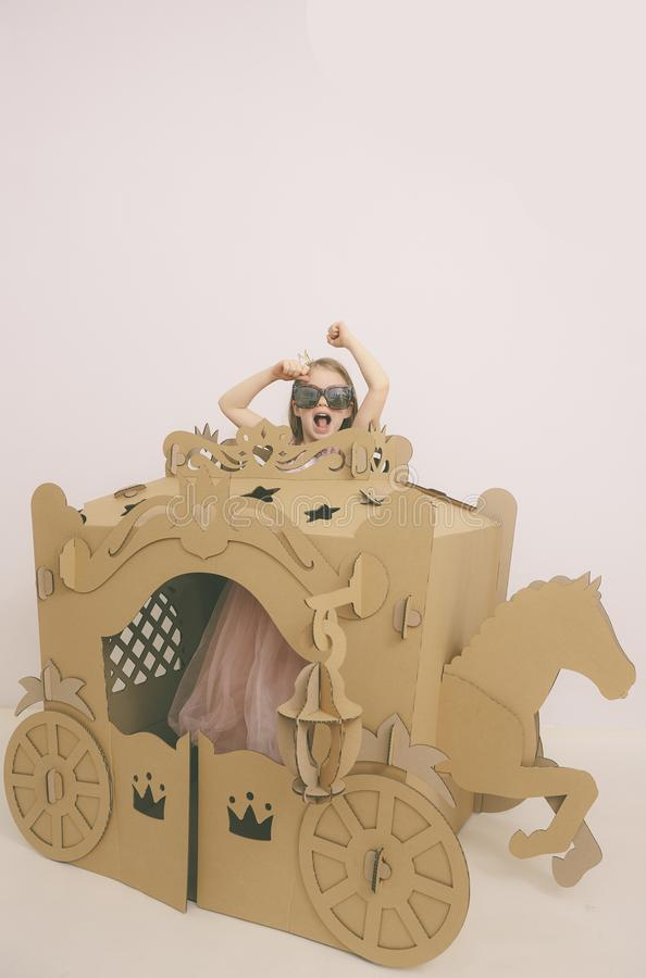 Pequeña muchacha caucásica linda en la princesa rosada en colores pastel Preparing para la fiesta de cumpleaños y presentación de fotografía de archivo