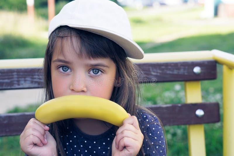 Pequeña muchacha caucásica que hace gesto triste con el plátano sobre fondo de la naturaleza Diversión y consumición sana foto de archivo libre de regalías