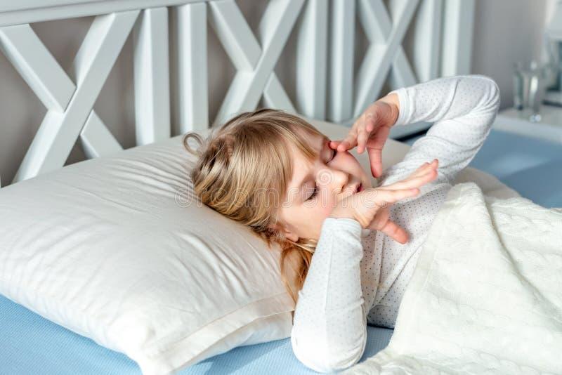 Pequeña muchacha caucásica rubia linda que despierta en la cama por mañana El niño despierta temprano para ir a la escuela El est imágenes de archivo libres de regalías
