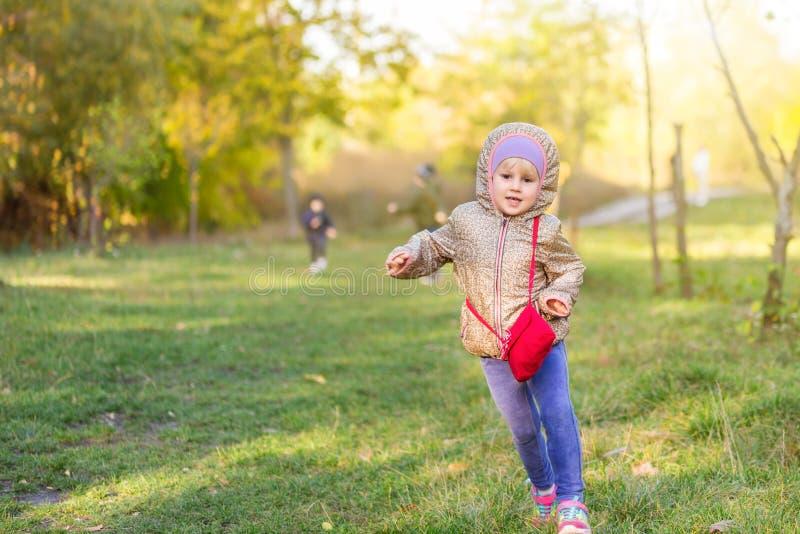 Pequeña muchacha caucásica rubia que corre en parque o bosque en día brillante del otoño Niño que se divierte que juega al aire l imagen de archivo