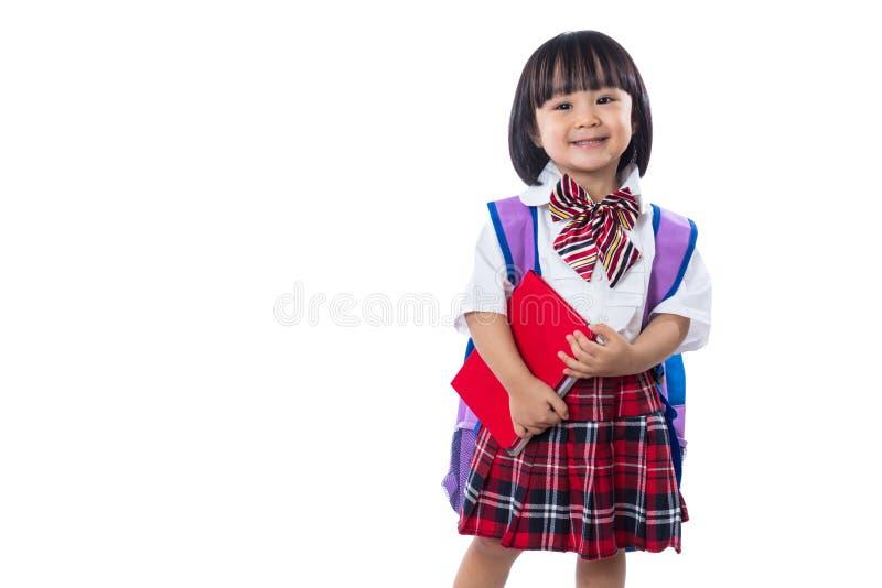 Pequeña muchacha china asiática del estudiante con el bolso y los libros de escuela fotos de archivo