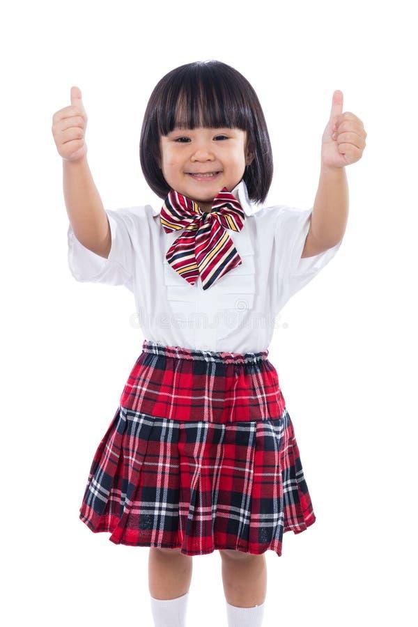 Pequeña muchacha china asiática feliz del estudiante que muestra los pulgares para arriba imagenes de archivo