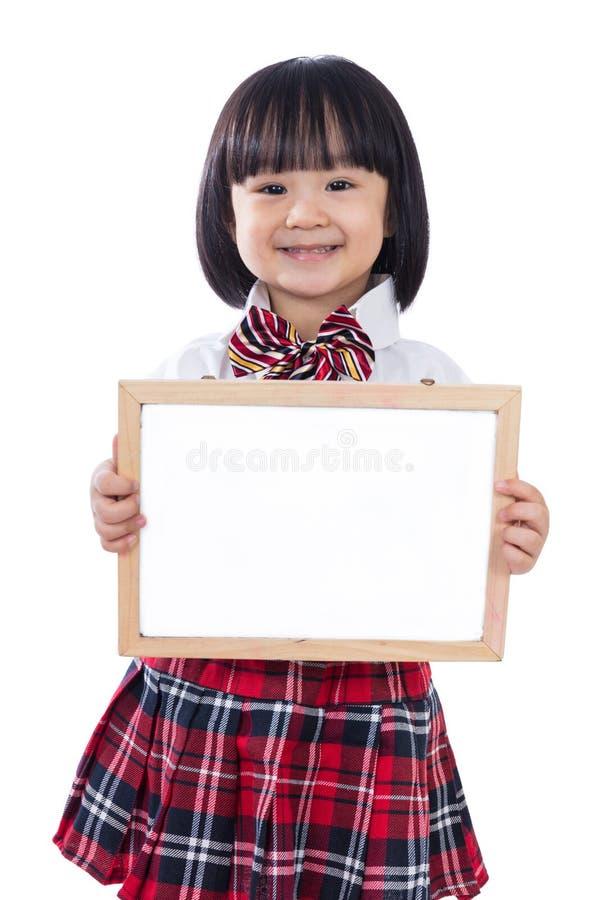 Pequeña muchacha china asiática feliz del estudiante que sostiene whiteboard fotografía de archivo libre de regalías