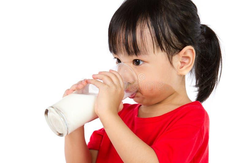 Pequeña muchacha china asiática que bebe una taza de leche foto de archivo libre de regalías