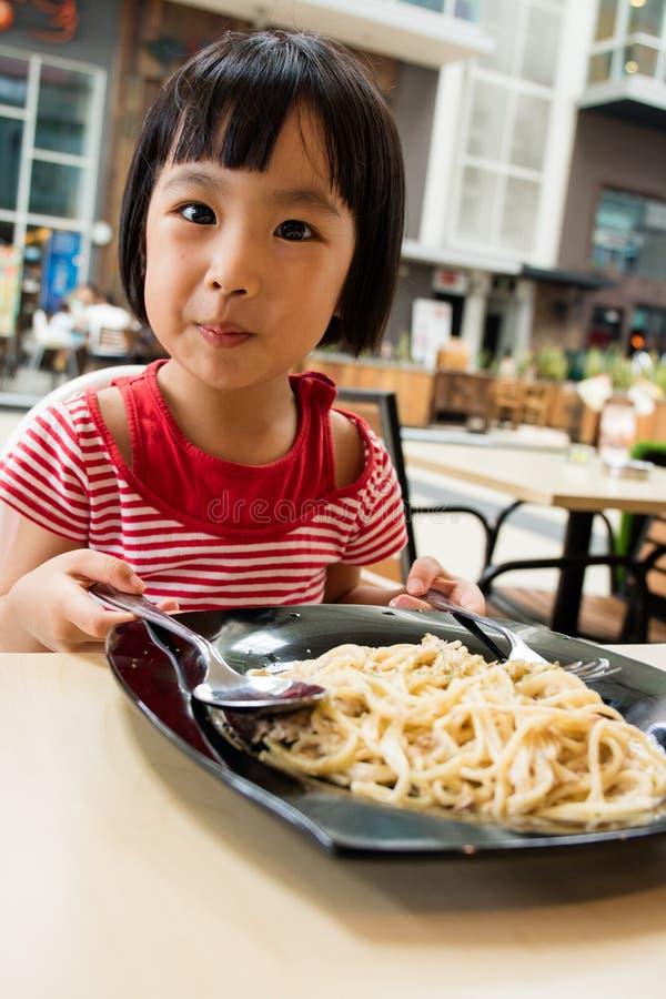 Pequeña muchacha china asiática que come los espaguetis foto de archivo libre de regalías