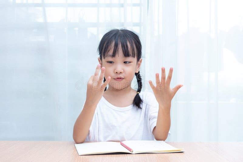 Pequeña muchacha china asiática que hace matemáticas contando los fingeres foto de archivo libre de regalías