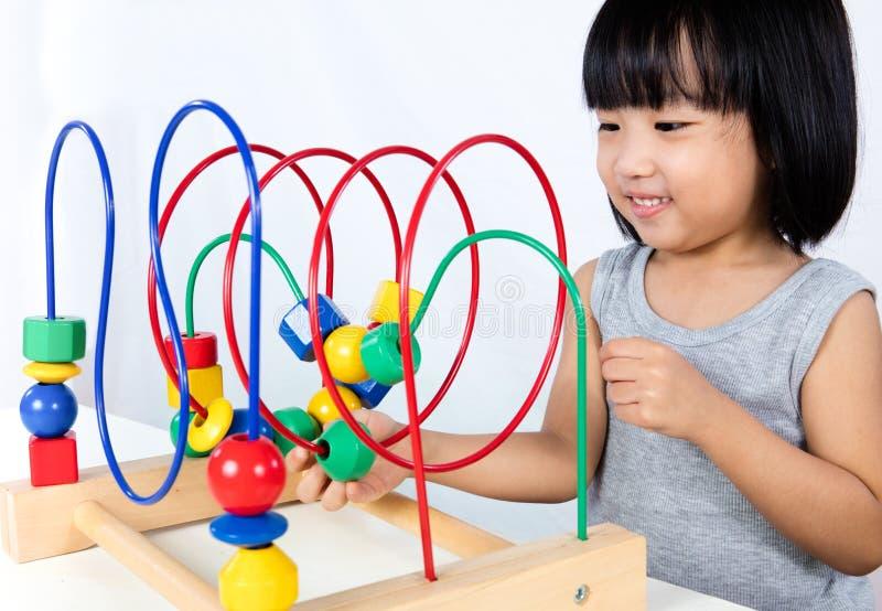 Pequeña muchacha china asiática que juega el juguete educativo colorido imagenes de archivo