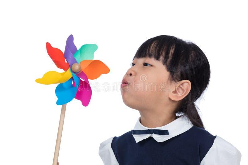 Pequeña muchacha china asiática que juega el molinillo de viento colorido fotografía de archivo