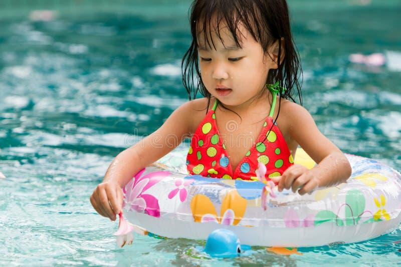 Pequeña muchacha china asiática que juega en piscina imagen de archivo libre de regalías