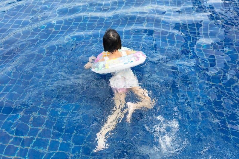 Pequeña muchacha china asiática que juega en piscina imagenes de archivo