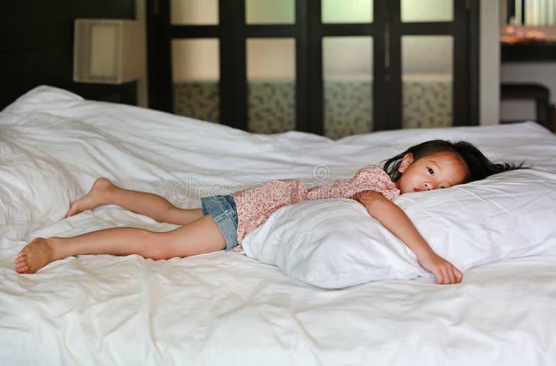 Pequeña muchacha china asiática que miente en la cama en casa con la mirada de la cámara imágenes de archivo libres de regalías