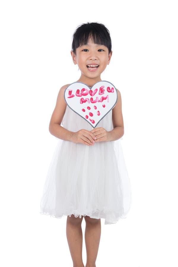 Pequeña muchacha china asiática que sostiene la tarjeta de felicitación para el día del ` s de la madre fotografía de archivo libre de regalías