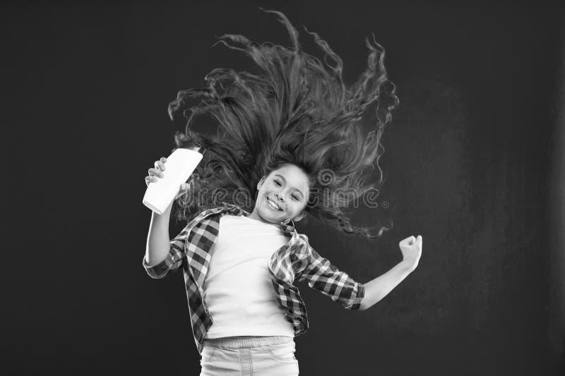 Pequeña muchacha con el pelo rizado largo Niño de la niña en fondo rojo Niñez salón y belleza del peluquero champú foto de archivo libre de regalías