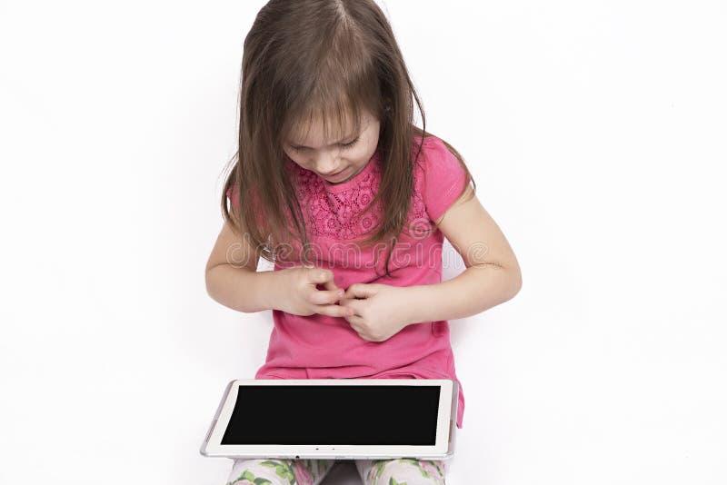 Pequeña muchacha con la tableta en el fondo blanco imagenes de archivo