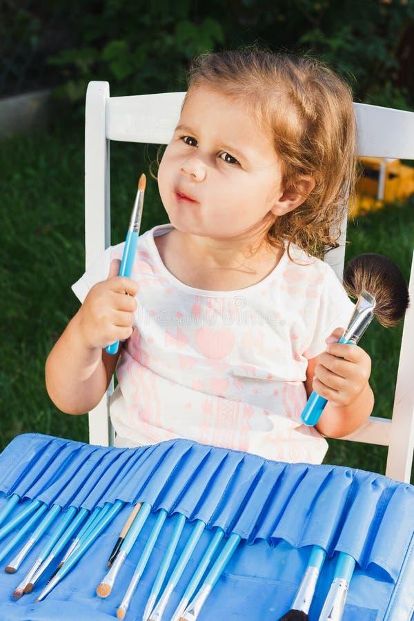 Pequeña muchacha con los cepillos de la belleza fotos de archivo
