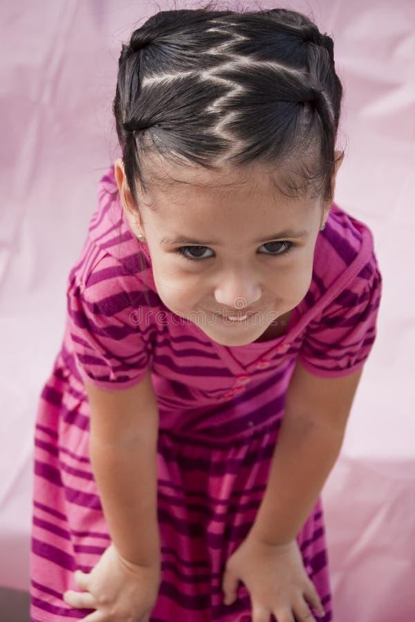 Pequeña muchacha con sonrisa de tomadura de pelo foto de archivo