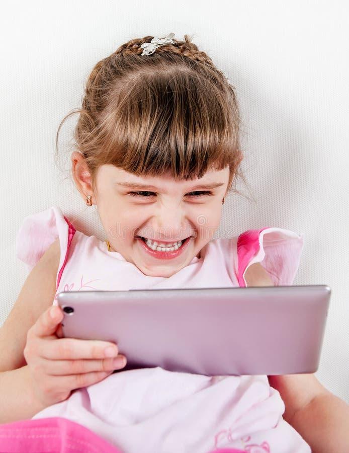 Pequeña muchacha con una tableta imagen de archivo