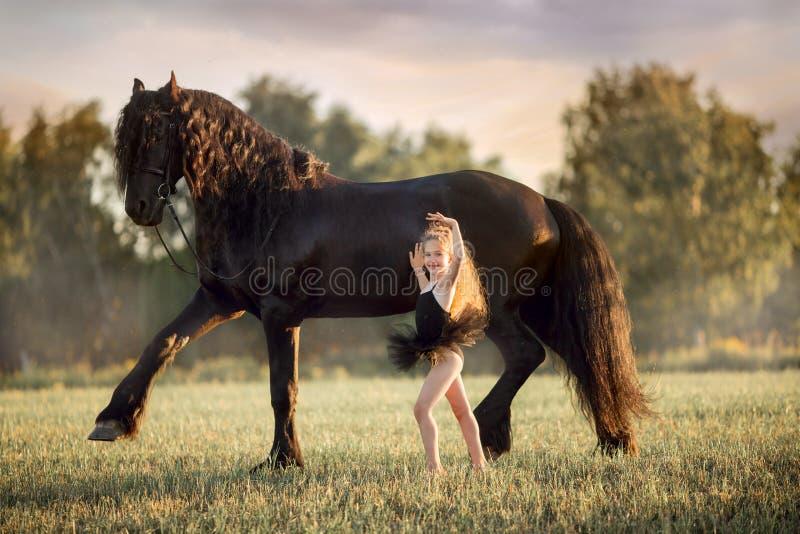 Pequeña muchacha de la bailarina con el semental frisio negro fotografía de archivo libre de regalías