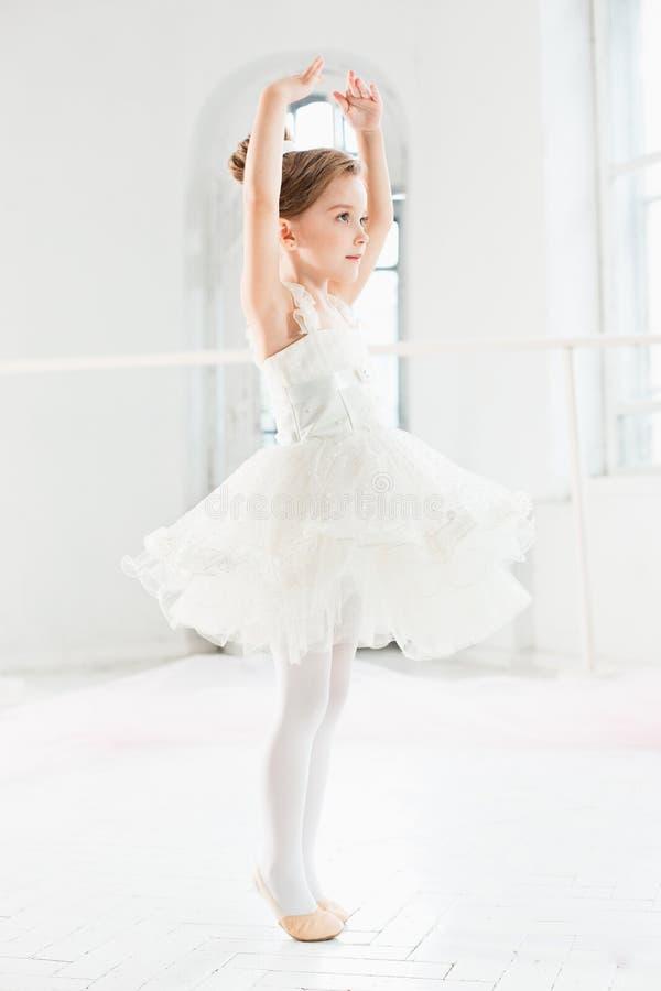 Pequeña muchacha de la bailarina en un tutú Niño adorable que baila ballet clásico en un estudio blanco imagenes de archivo