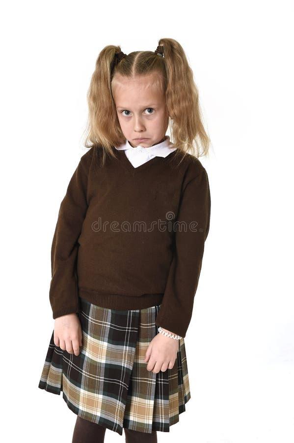 Pequeña muchacha de la colegiala con el pelo rubio hermoso en el uniforme escolar que parece tímido y tímido fotos de archivo libres de regalías