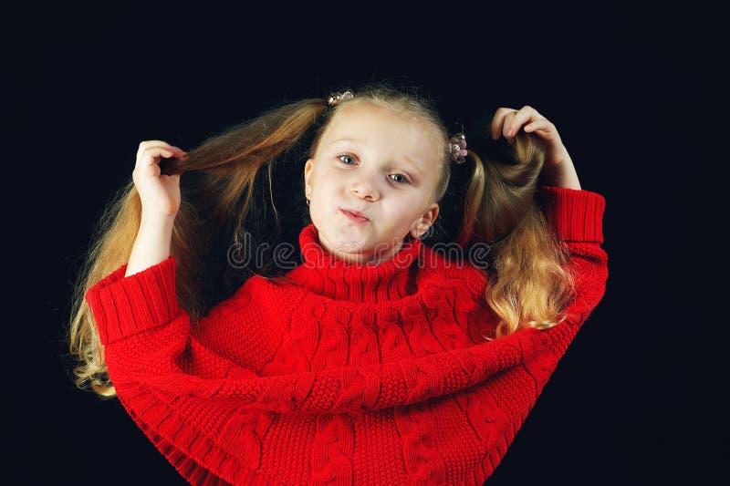 Pequeña muchacha de moda en el suéter rojo que sostiene un pelo imagen de archivo libre de regalías